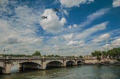 Aperçu des avions militaires passant par le ciel obscurci au-dessus du pont de la Seine à Paris Photos stock