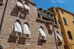 Aperçu des fenêtres dans le vieil immeuble de brique avec des abat-jour de tissu à Venise Images stock