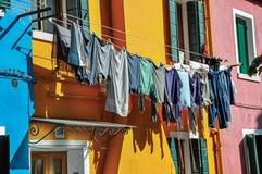 Aperçu des maisons colorées et des vêtements en terrasse accrochant dans une allée dans Burano Image stock