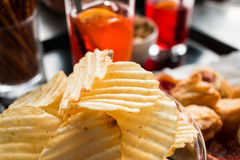 Aperitif in the bar. Close-up of a typical drink at the bar. Italian style. chips in the foreground, the background soft drinks and snacks all in glasses Stock Image
