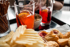 Aperitif in the bar. Tray ready for the appetizer, chips blurry in the foreground, drinks, snacks and pizzas in focus. an open hand in the background, glasses Stock Photos