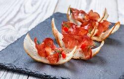 Aperitif bruschetta mit stoßartigem Prosciutto auf dünn geschnittenem ciabatta Brot auf Steinschieferhintergrundabschluß oben Stockfotos