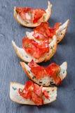 Aperitif bruschetta mit stoßartigem Prosciutto auf dünn geschnittenem ciabatta Brot auf Steinschieferhintergrundabschluß oben Lizenzfreies Stockfoto