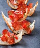 Aperitif bruschetta mit stoßartigem Prosciutto auf dünn geschnittenem ciabatta Brot auf Steinschieferhintergrundabschluß oben Stockbilder