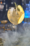 Aperitif cocktail with orange and rosemary. In the smoke at the front bartending royalty free stock photos