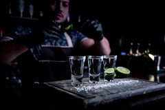Aperitif with friends in the bar, three glasses of alcohol with lime and salt for decoration. Tequila shots, selective. Focus stock photos