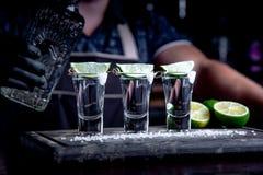 Aperitif med vänner i stången, tre exponeringsglas av alkohol med limefrukt och att salta för garnering Tequilaskott som är selek arkivbilder