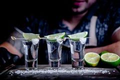Aperitif med vänner i stången, tre exponeringsglas av alkohol med limefrukt och att salta för garnering Tequilaskott som är selek arkivbild