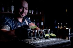 Aperitif med vänner i stången, tre exponeringsglas av alkohol med limefrukt och att salta för garnering Tequilaskott som är selek royaltyfri fotografi