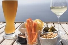 Aperitif on the sea. Bier and wine with some food like olives, carrots, peanuts and a wonderful view in italy, liguria country stock photos