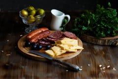 Aperitif stołowa Mięsna przekąska, smażyć kiełbasy, ser, salami, oliwki i szkło wino na zmroku stole, zdjęcia stock