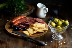 Aperitif table Meat snack, fried sausages, cheese, salami, olives and a glass of wine on a dark table royalty free stock photo