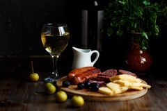 Aperitif table Meat snack, fried sausages, cheese, salami, olives and a glass of wine on a dark table Menu and restaurant concept stock images