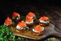 Aperitif von Lachsen auf Kartoffelpfannkuchen mit Käse lizenzfreie stockfotos