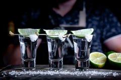 Aperitif z przyjaciółmi w barze, trzy szkłach alkohol z wapnem i soli dla dekoracji, Tequila strzały, selekcyjni obrazy stock