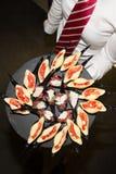 Aperitifs in einem Teller geholt vom Kellner lizenzfreies stockfoto