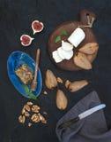 Aperitifsatz Gebratene Birnen, Ziegenkäse auf rustikalem dunklem hölzernem Brett, Feige, Honig und Walnüsse über schwarzem Stein Stockbild