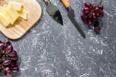 Aperitive parmesan cheese and red grape on grey stone table background copyspace top view. Aperitive parmesan cheese and red grape on grey stone table background Royalty Free Stock Image