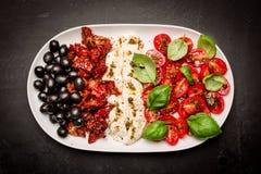Aperitivi italiani - mozzarella, pomodori, olive e basilico Immagine Stock
