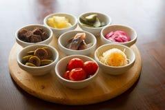 Aperitivi in piccoli piatti su fondo marrone immagini stock