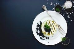Aperitivo con el caviar negro en el fondo negro, servicio del ejemplo Fotos de archivo