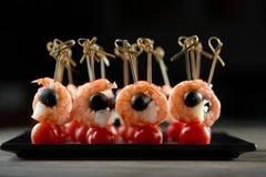 Aperitivo con los camarones, las aceitunas y los tomates Foto de archivo libre de regalías