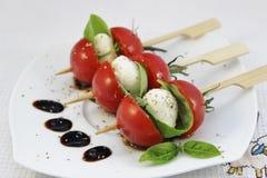 Aperitivo con los tomates de la mozzarella y del cóctel del bebé en los pinchos Imagenes de archivo