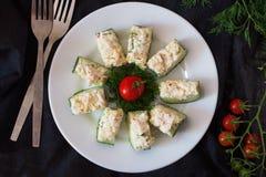 Aperitivo da un cetriolo fresco con polpa di granchio, l'uovo, il formaggio e l'aneto immagine stock