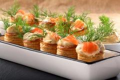 Aperitivo de color salmón con la inmersión del eneldo en pasta de hojaldre en la bandeja de piedra Fotografía de archivo