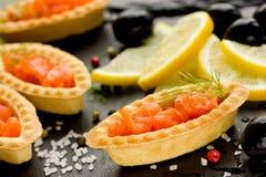 Aperitivo de color salmón en tartlets con la sal, el limón y las aceitunas negras Imagen de archivo