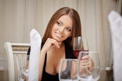 Aperitivo de consumición sonriente de la mujer en restaurante Foto de archivo