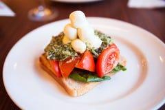 Aperitivo de la mozzarella, de la tostada, del pesto y del tomate Foto de archivo libre de regalías