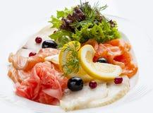 Aperitivo de pescados salados en el fondo blanco foto de archivo