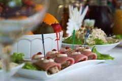 Aperitivo de rollos con el jamón en la tabla del día de fiesta Fotografía de archivo