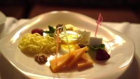 Aperitivo del queso en la placa blanca en restaurante de la playa en verano sano y delicioso de las vacaciones de la comida almacen de metraje de vídeo