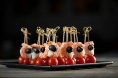 Aperitivo delicioso con los camarones, las aceitunas y los tomates Imagen de archivo