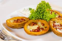 Aperitivo della patata al forno guarnita con formaggio e bacon immagini stock
