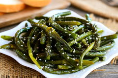 Aperitivo fritto delle frecce dell'aglio Frecce verdi piccanti dell'aglio con le spezie ed i semi di sesamo su un piatto Facile,  Immagine Stock Libera da Diritti