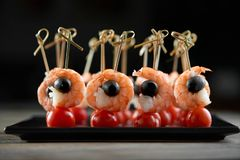 Aperitivo sabroso con los camarones, las aceitunas y los tomates Imagenes de archivo