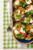 Aperitivos - berenjenas asadas a la parrilla con ajo, queso feta y tomates foto de archivo
