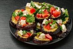 Aperitivos - berenjenas asadas a la parrilla con ajo, queso feta y tomates imagen de archivo