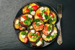 Aperitivos - berenjenas asadas a la parrilla con ajo, queso feta y tomates imagenes de archivo