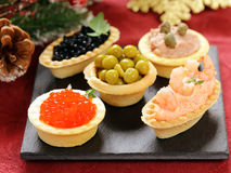 Aperitivos de la Navidad Pequeños tartlets con el caviar y la coronilla Fotografía de archivo libre de regalías