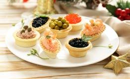 Aperitivos de la Navidad Pequeños tartlets con el caviar y la coronilla Foto de archivo