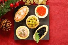 Aperitivos de la Navidad Pequeños tartlets con el caviar y la coronilla Fotos de archivo