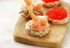 Aperitivos de la Navidad Pequeños tartlets con el caviar y la coronilla Fotografía de archivo