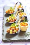 Aperitivos del día de fiesta con el caviar de color salmón y rojo Imagen de archivo libre de regalías