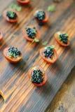 Aperitivos negros del caviar en el tablero de madera Fotos de archivo
