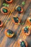 Aperitivos negros del caviar en el tablero de madera Fotografía de archivo