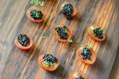 Aperitivos negros del caviar en el tablero de madera Imágenes de archivo libres de regalías